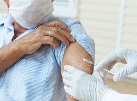 homme âgé masqué recevant une dose de vaccin