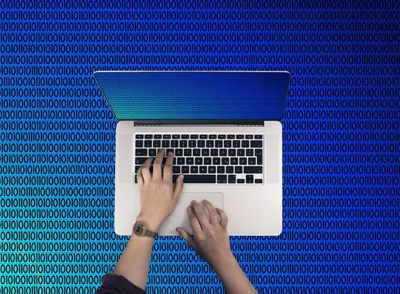 mains tapant sur un clavier d'ordinateur et code binaire