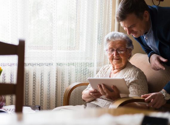 Dame âgée apprenant à utiliser une tablette numérique