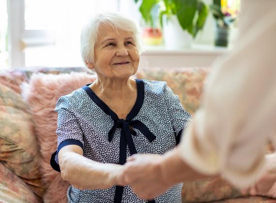 Dame âgée se levant d'un sofa avec l'aide d'une soignante