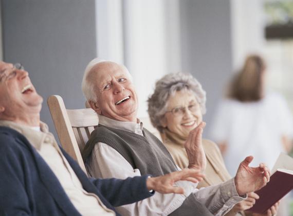 3 personnes âgées qui rient sous un porche